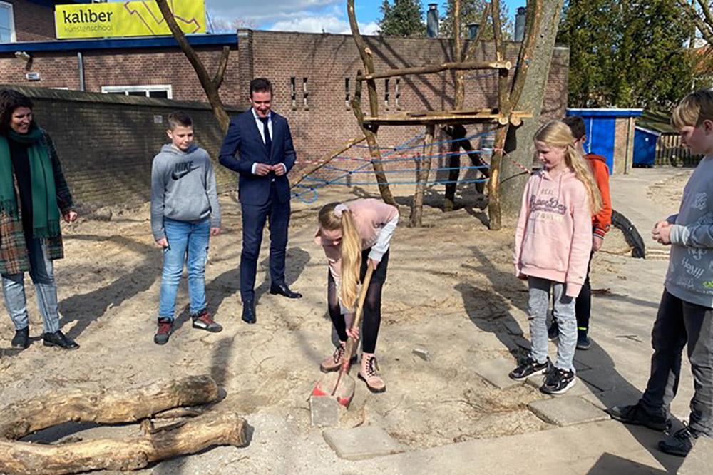 Samen met de leerlingen van groep 8 zet wethouder Eugène van Mierlo de eerste schop in de grond (Foto- RTV Oost)